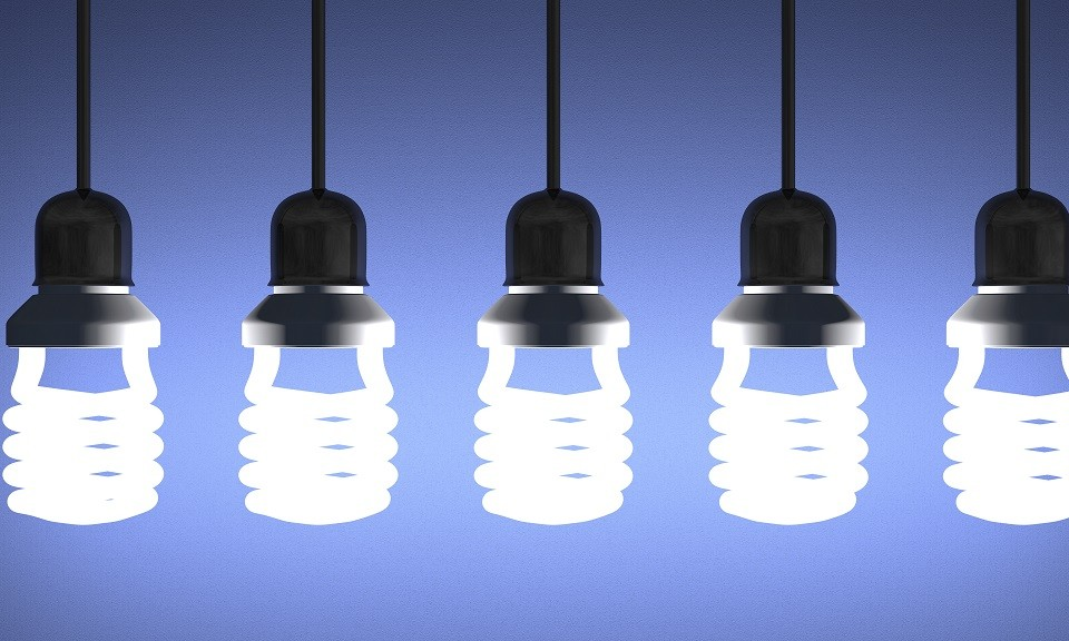 Glowing fluorescent light bulbs installed in sockets hanging on wires on blue textured background