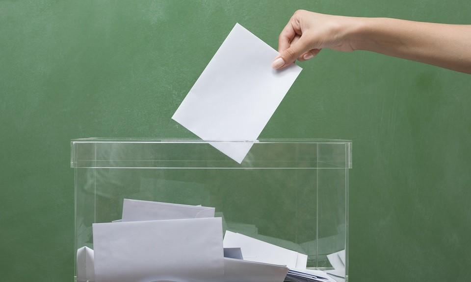 Voting for election in front of black blackboard