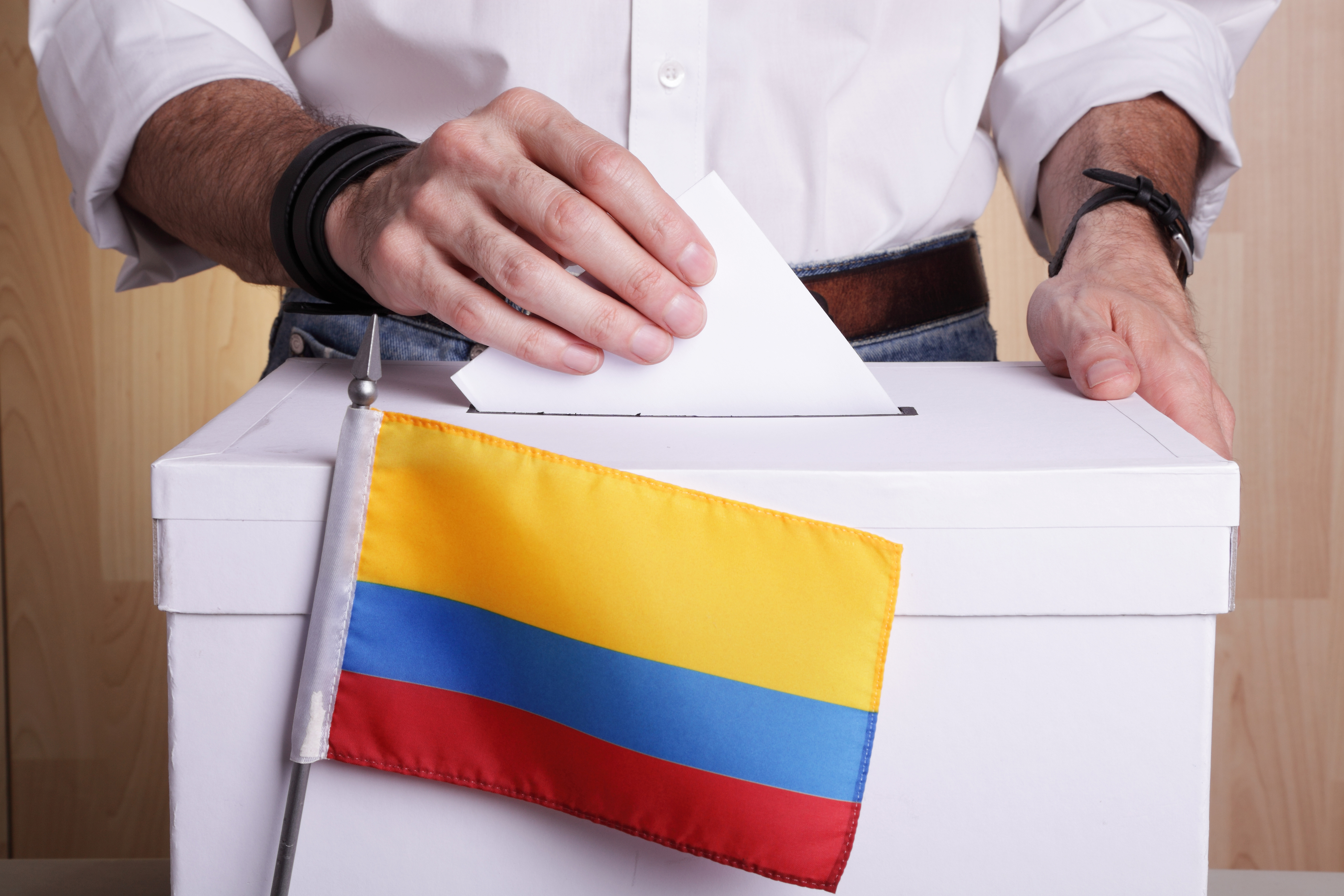A man inserting a ballot to a ballot box.  Colombian flag in front of it.