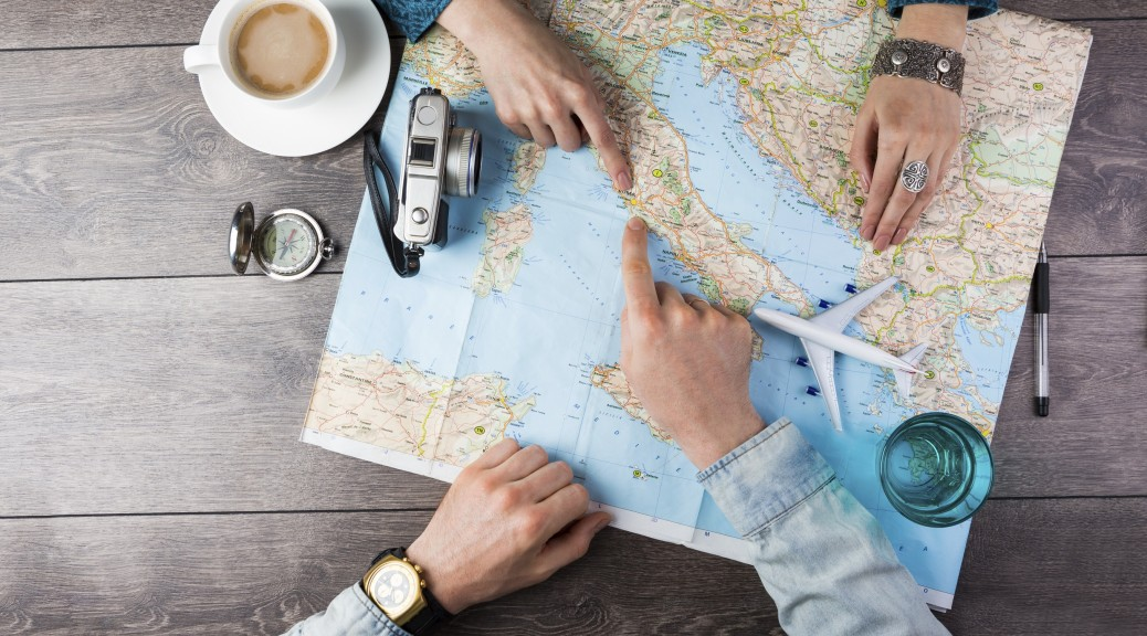 Young couple planning honeymoon vacation trip with map. Top view. Pointing to Europe Rome