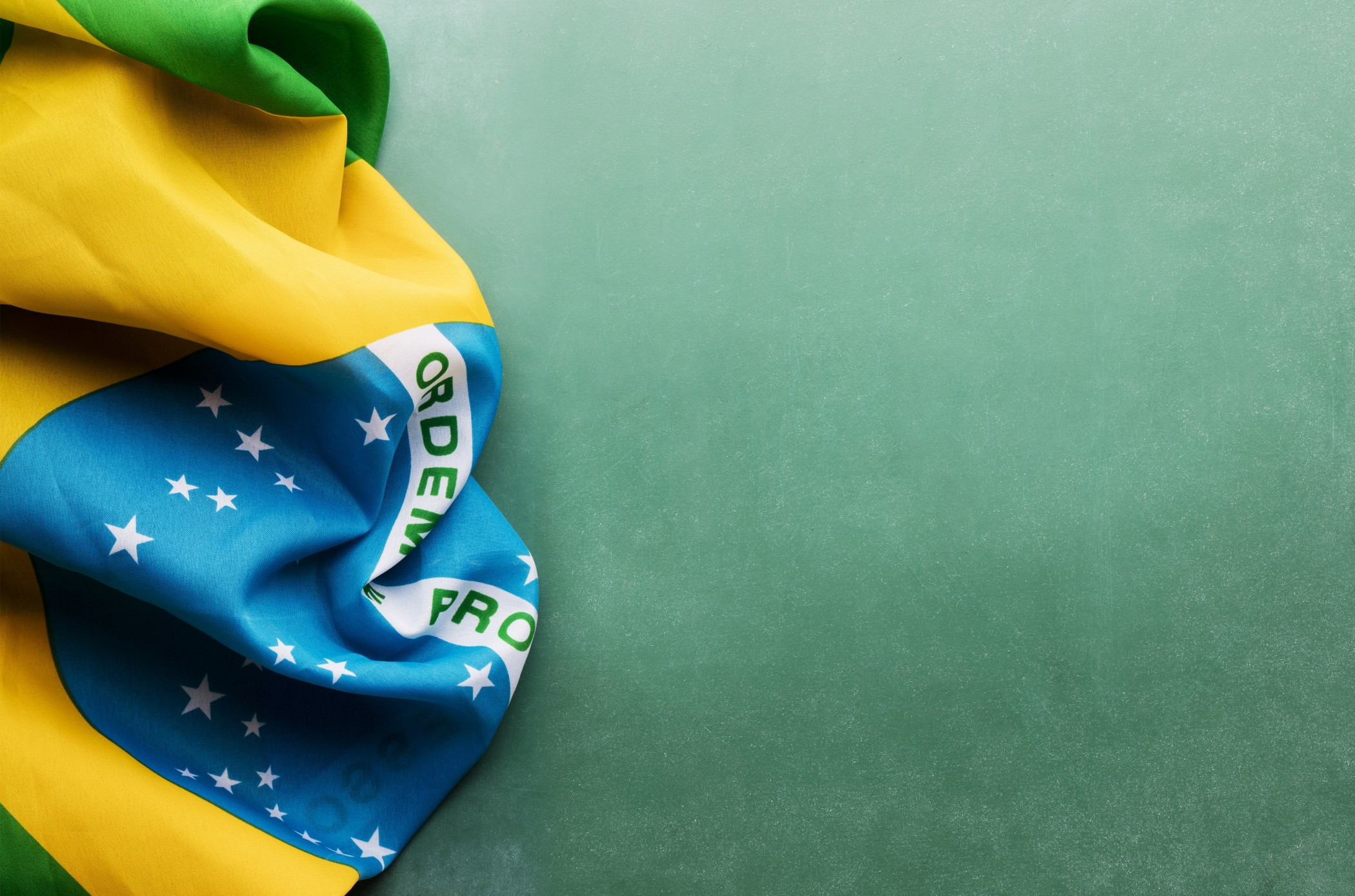 A Brazil flag is laying on a green chalkboard background