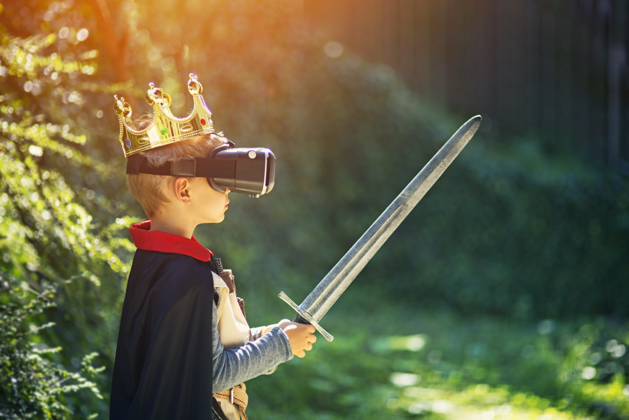Little boy having fun playing with virtual reality headset. The boy aged 6 is standing outdoors or in cyberspace generated forest. The boy is wearing king's crown and knight outfit and is holding a sword.