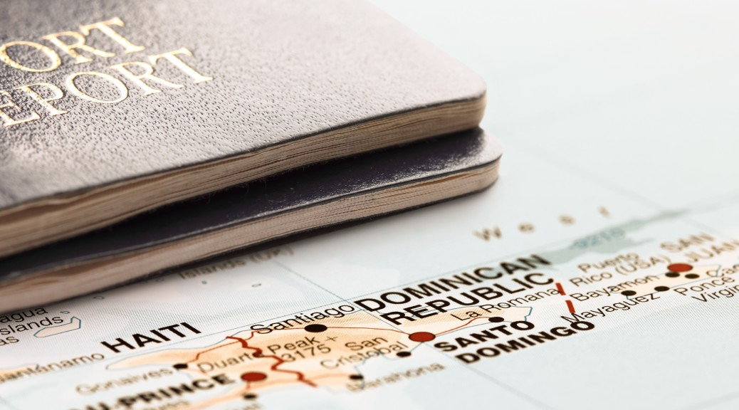 Two passports on the map of Dominican Republic, are ready for travel. The map is toned in pastel colors. Concept: Planning travel destinations or journey planning. Close-up view. Studio shot. Landscape orientation.