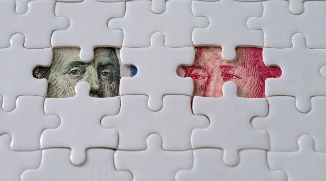 US and Chinese paper currency under jigsaw puzzle