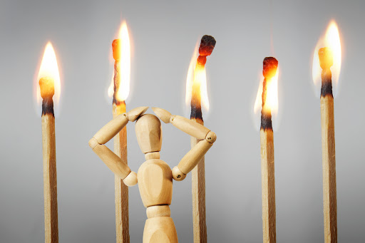 Man is afraid of fire. Abstract image with a wooden puppet