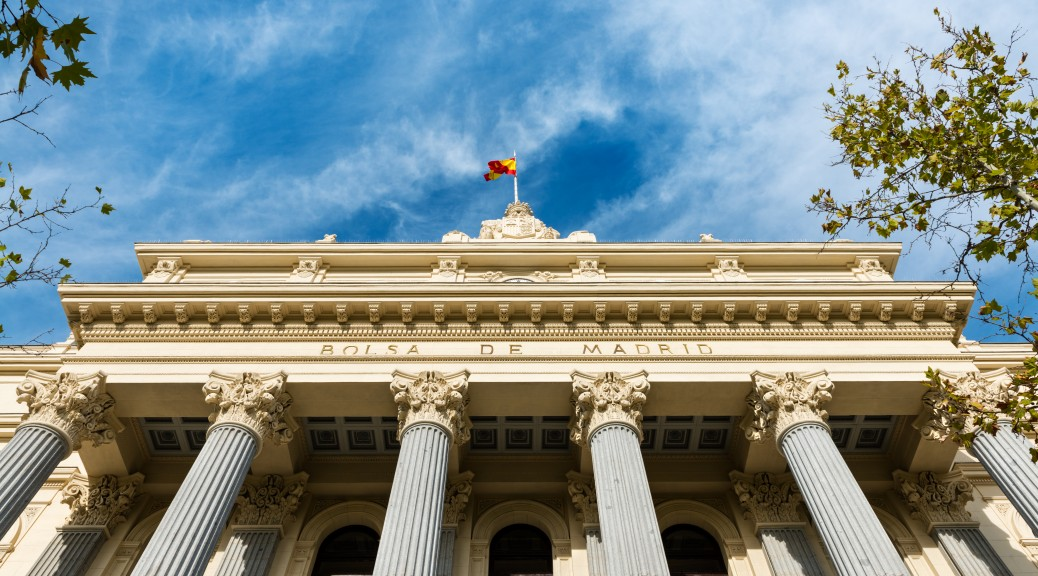 Madrid, Spain - September 25, 2015: Low-angle view of the columns and neoclassical facade of the Bolsa de Madrid (Madrid's Stock Exchange) against a cloudy blue sky.