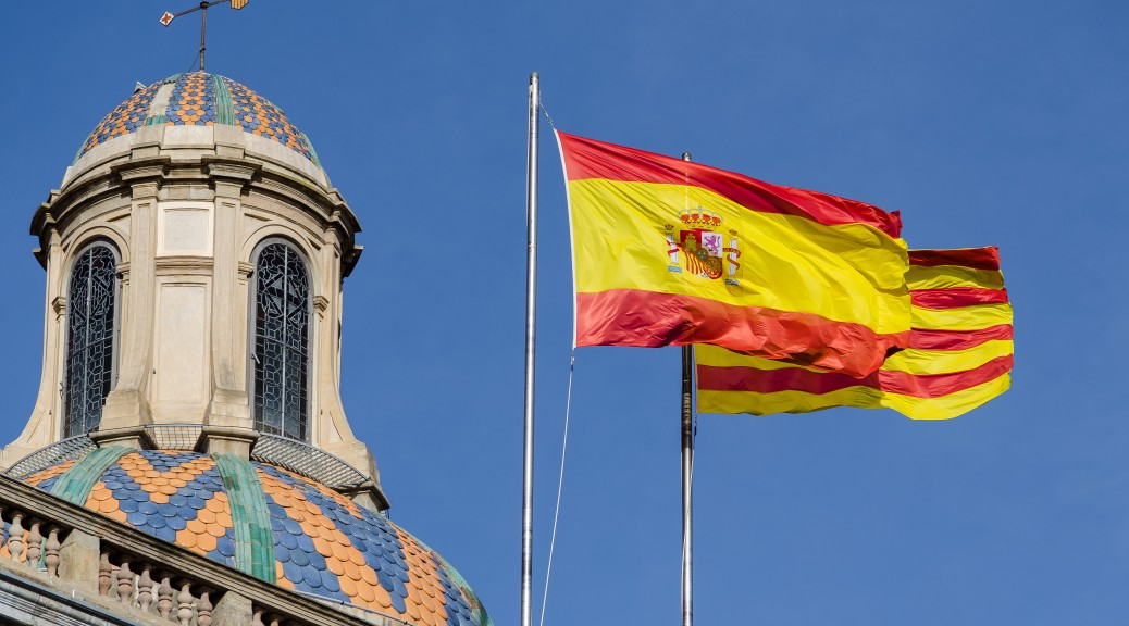 Two flags waving in the blue sky : Spanish and Catalan, and an old building dome beside, Picture taken in the streets of Barcelona, Spain